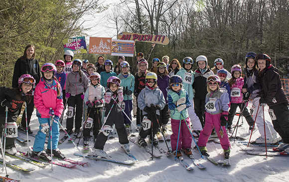Large group of girls wearing helmets, snow pants and ski jackets on skis with a snowy background.