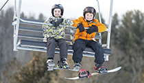 Two boys with big smiles riding the chairlift