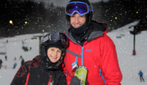 Dad and son skiers at bottom of trail